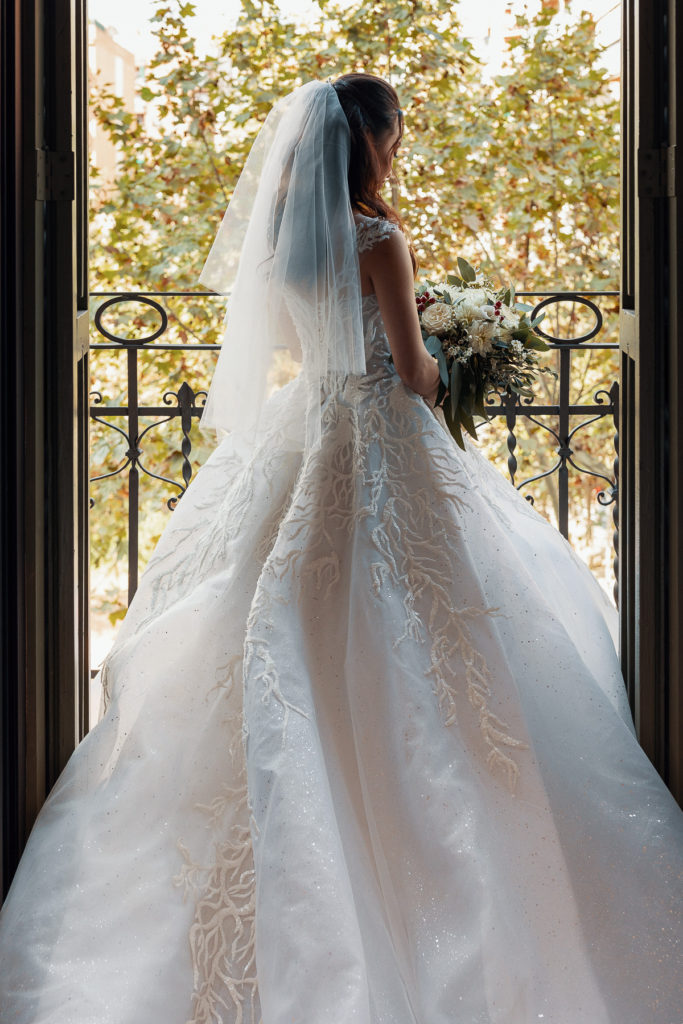 bride stands on balcony in dress and veil holding bouquet of white flowers
