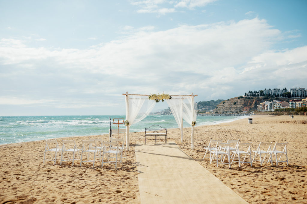 beach with white chairs and altar covered in white fabric