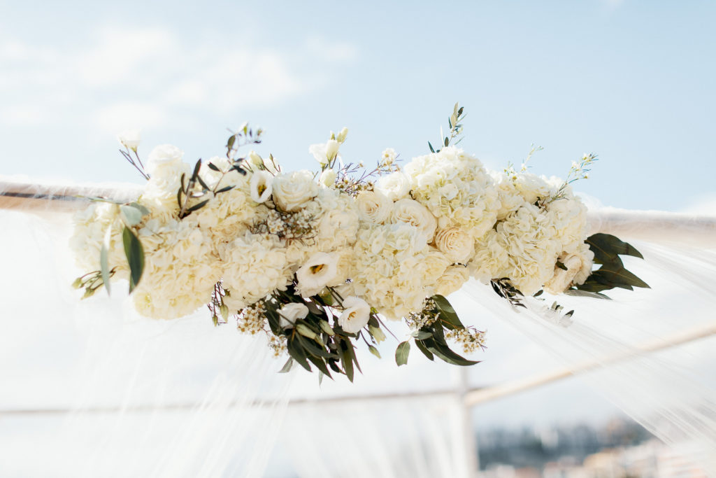 white flowers on the top of the chuppah