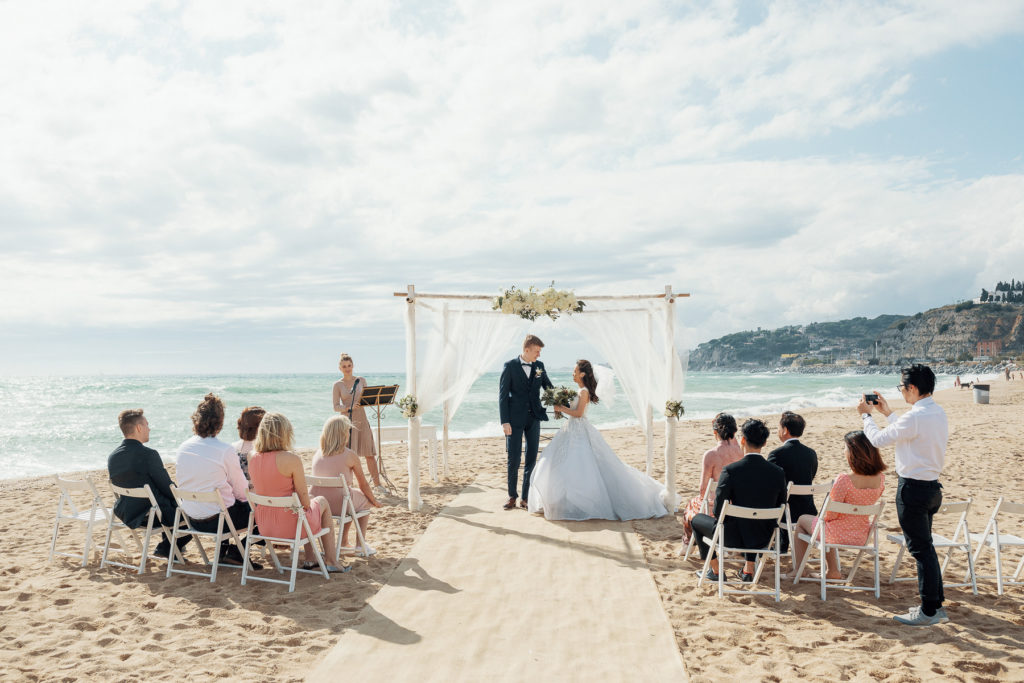 bride and groom stand beneath chuppah on beach in front of wedding guests