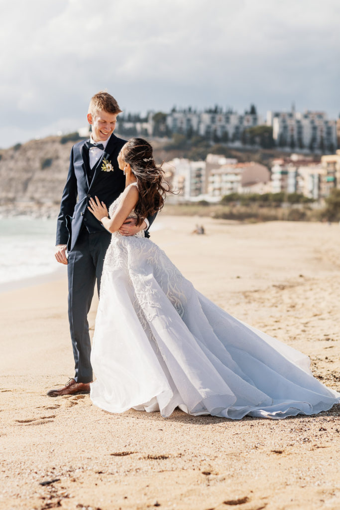 bride and groom embrace and smile on beach