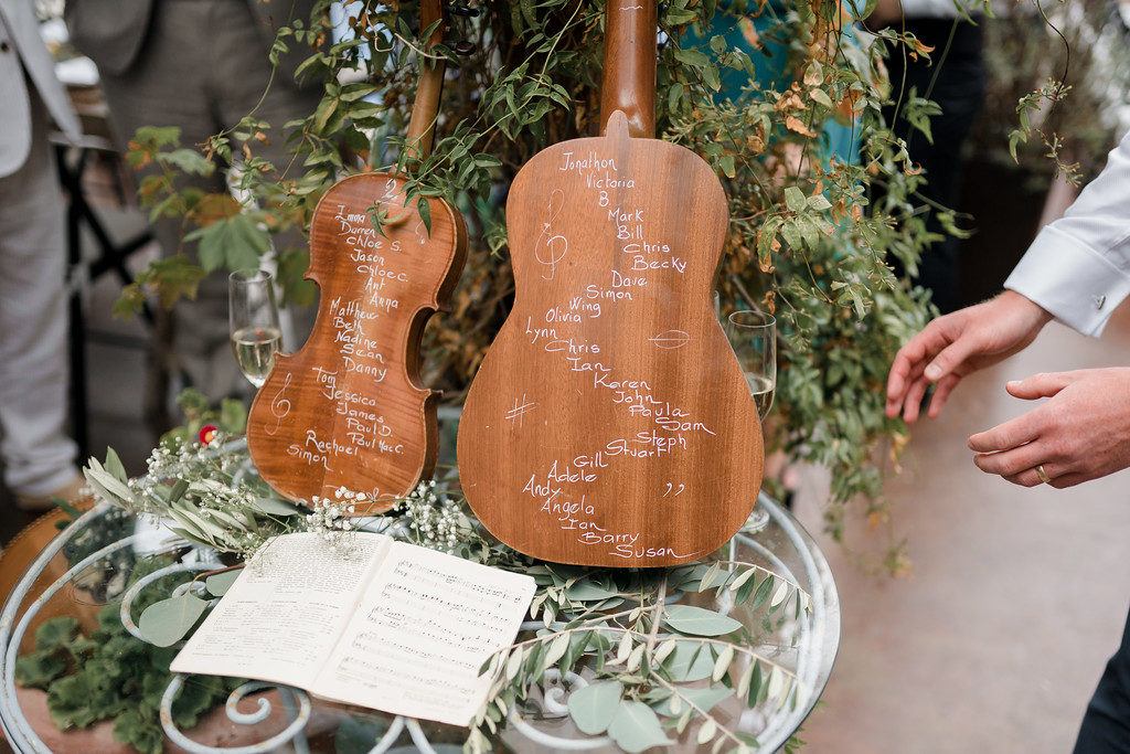 wedding guest list for tables written on back of guitar and violin, casa felix, barcelona brides