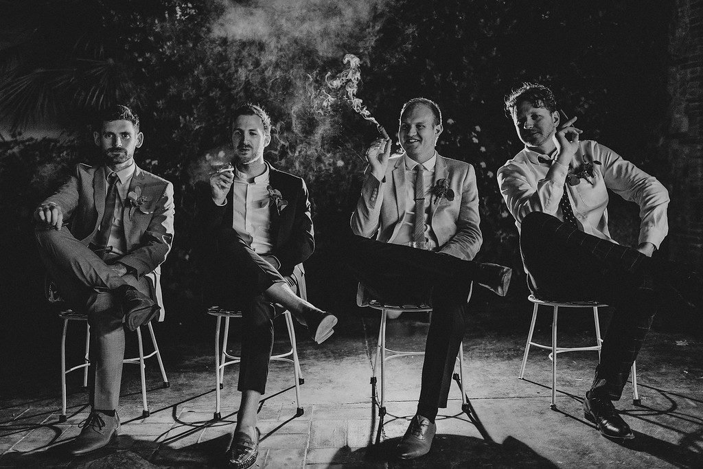 groom and groomsmen smoking cigars outside casa felix, barcelona, spain