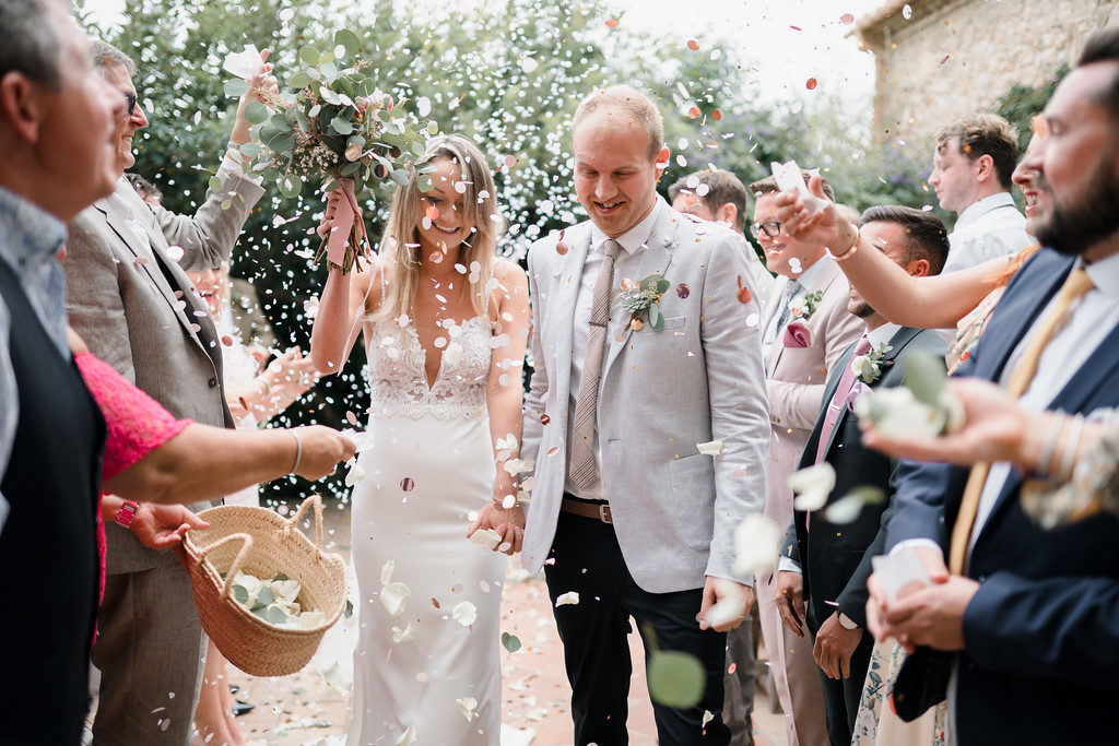 wedding guests shower bride and groom with flower petals outside casa felix, barcelona, spain