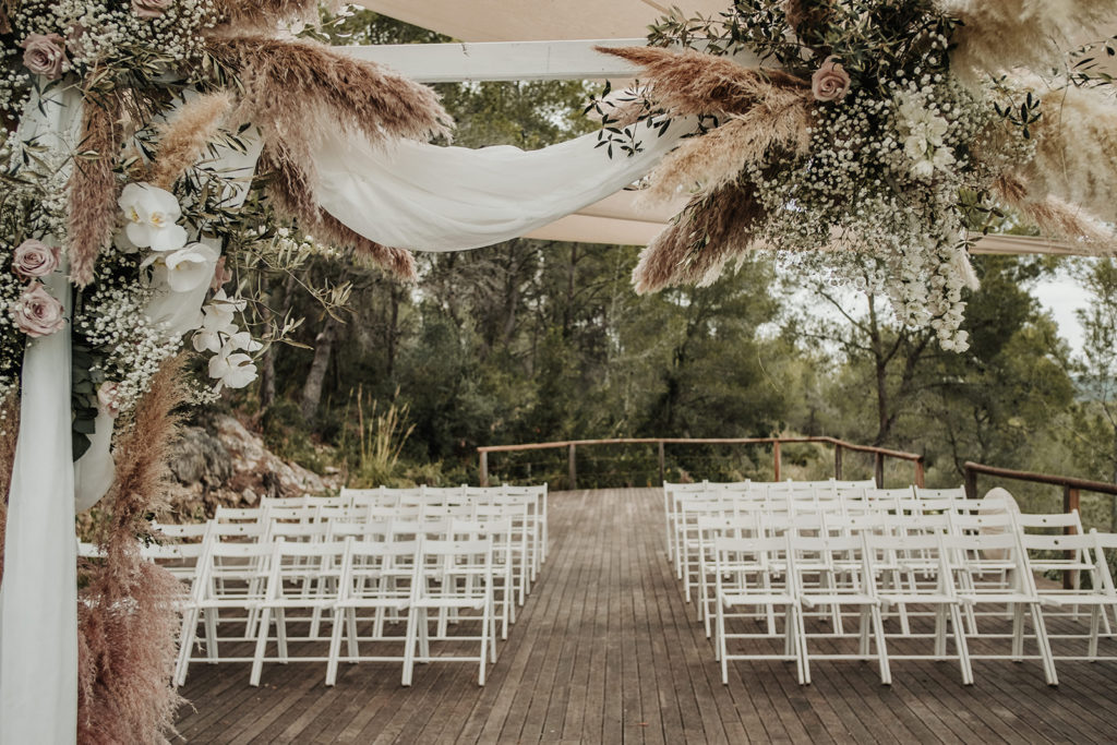 white chairs set up for wedding ceremony and floral arch with dusty roses and natural grasses, almiral de la font, barcelona brides