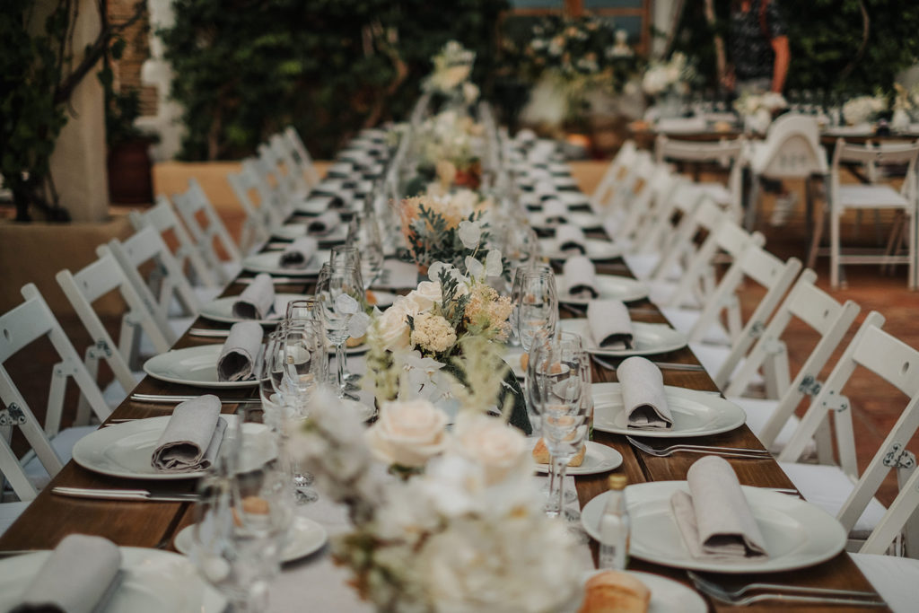 wedding table with white plates and linen napkins with white flowers in center, almiral de la font, barcelona brides
