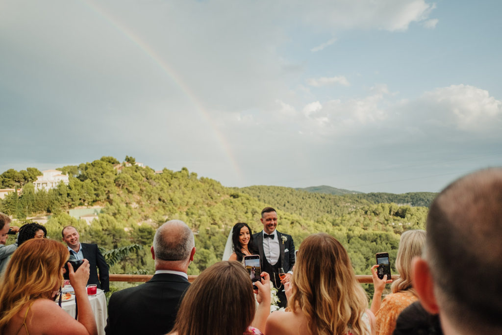 wedding guests taking photos of bride and groom beneath rainbow, almiral de la font, barcelona, spain