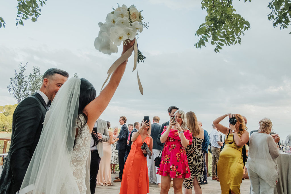 bride holds bouguet in air with groom and wedding guests take photos, almiral de la font, barcelona, spain