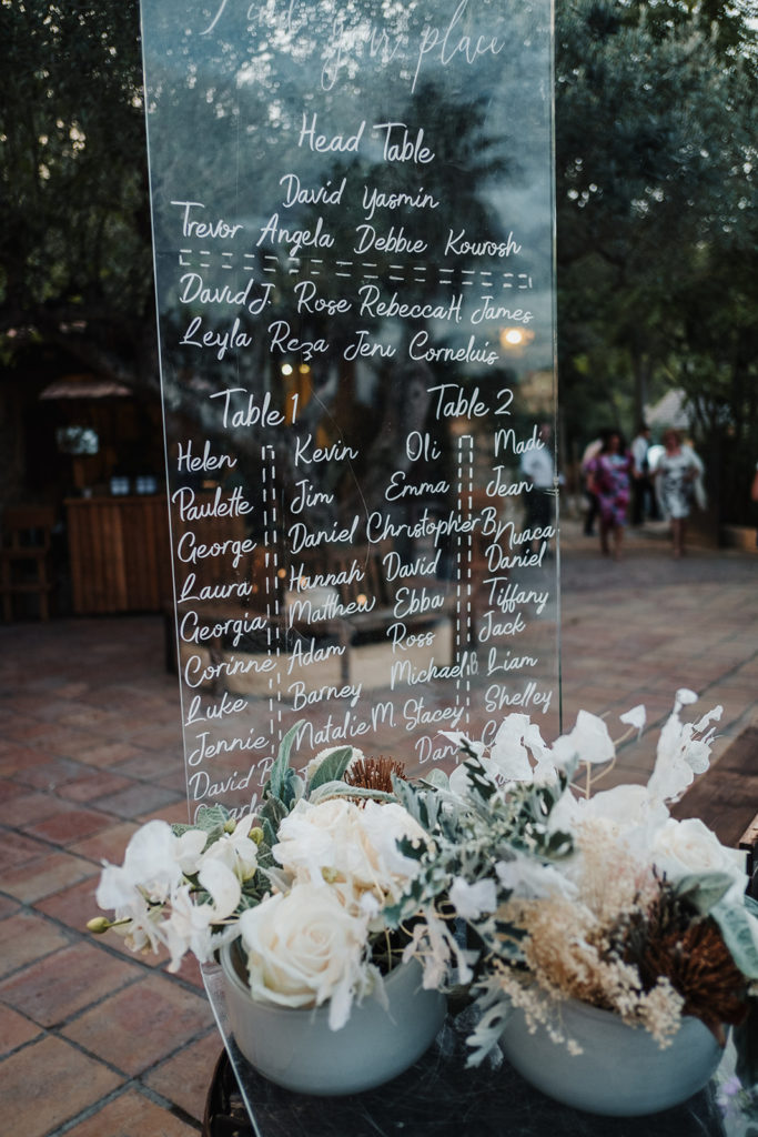 wedding table assignment chart written on glass with neutral florals, almiral de la font, barcelona brides, spain