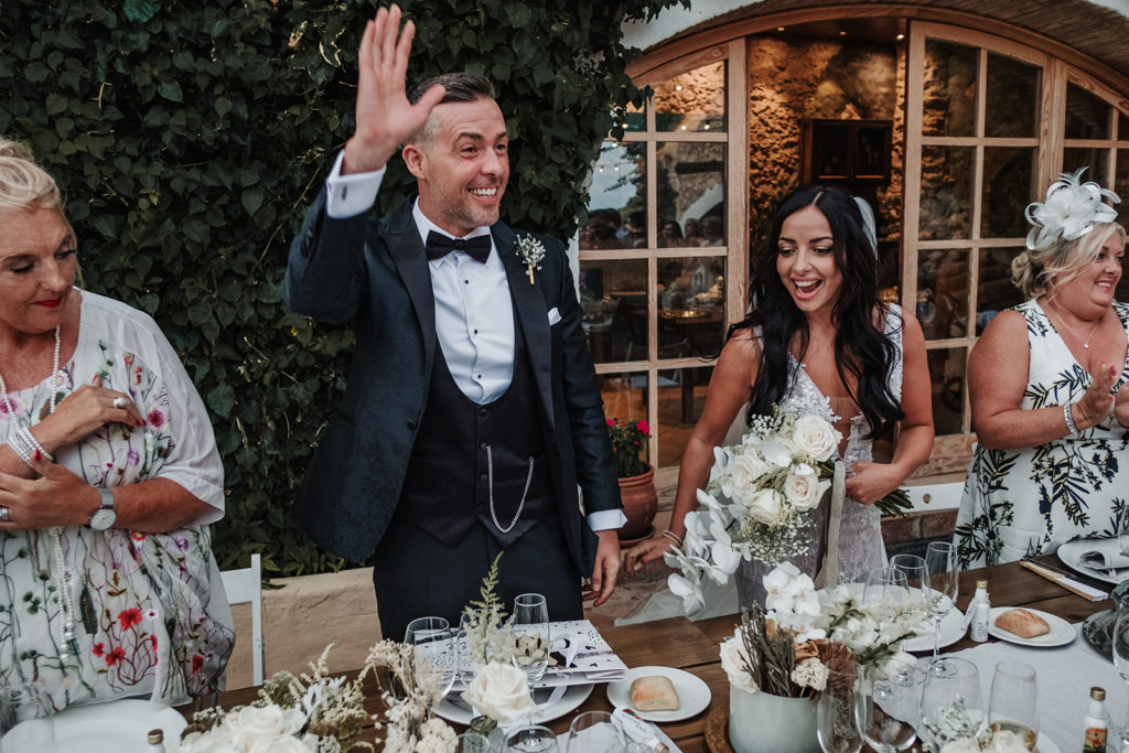 bride and groom find seats at dinner table, almiral de la font, barcelona, spain