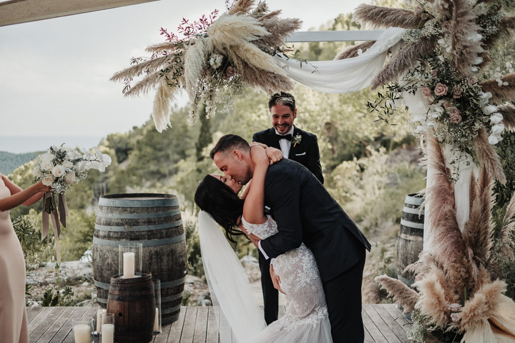 bride and groom kiss in front of floral arch at wedding ceremony, almiral de la font, barcelona, spain