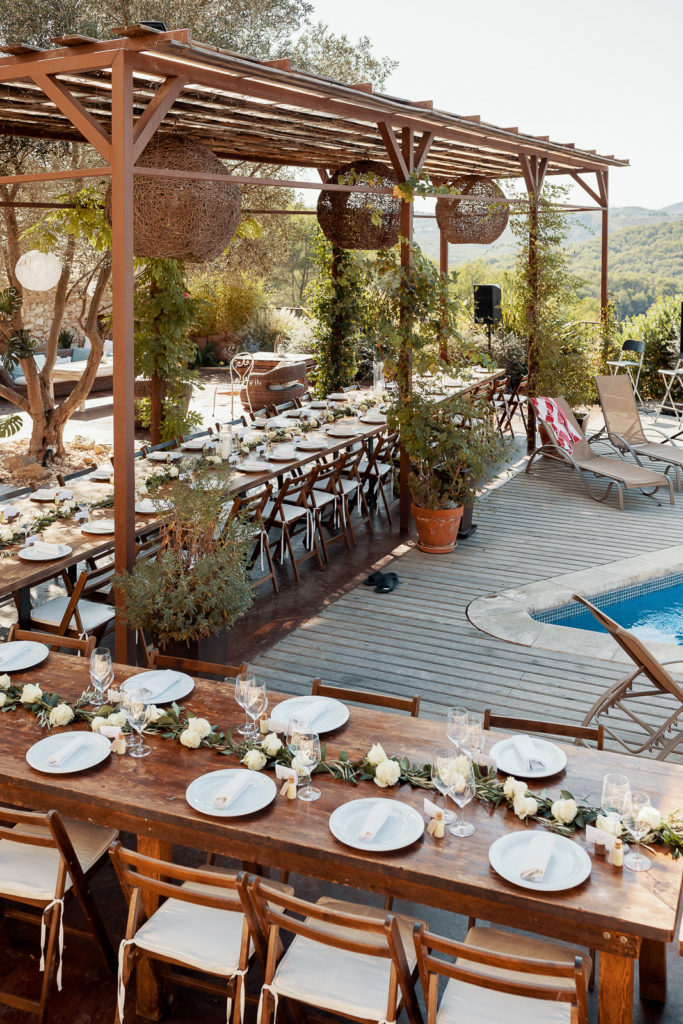 L shaped table with white flowers and settings near pool