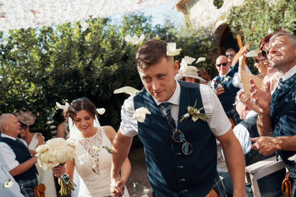 bride and groom walk down aisle with flower petals in the air