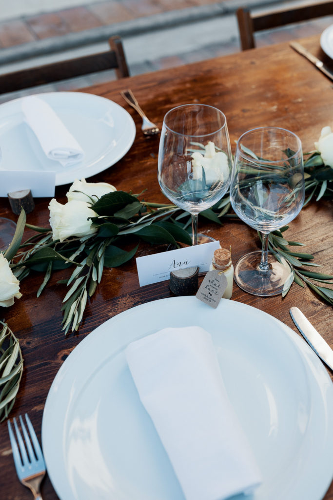 all white table setting with white roses, small bottle and cork and name tag that says Ann