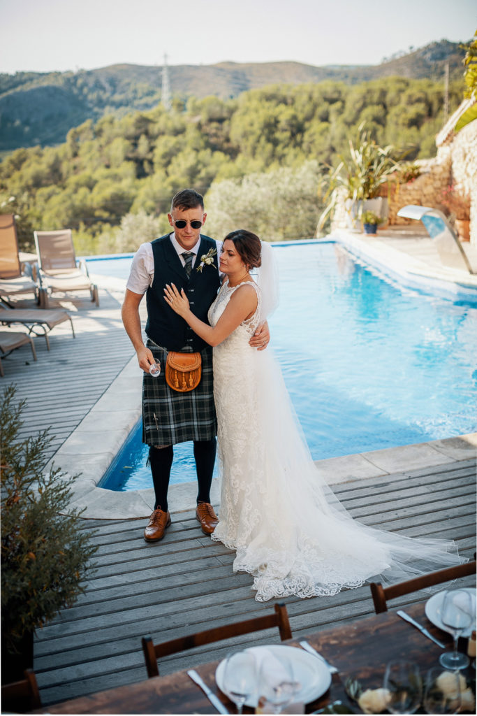 bride and groom embrace near pool