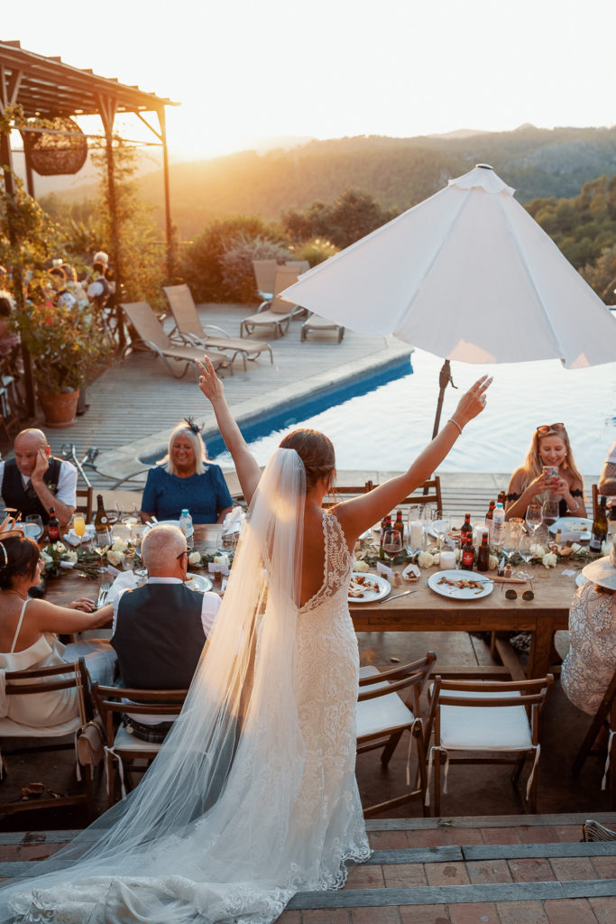 bride raises her hands up in front of guest at the dinner table