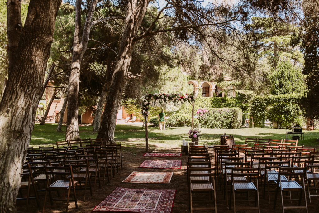 empty chairs face outdoor alter and rugs on the ground in the aisle