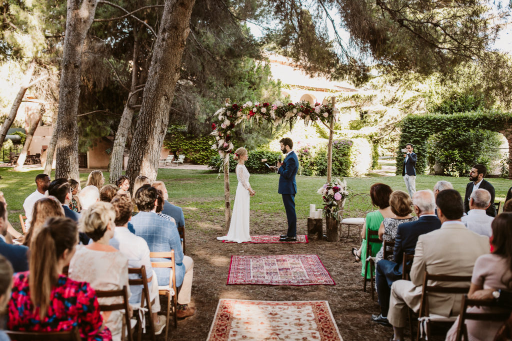 groom reads vows to bride in front of their outdoor altar and guests