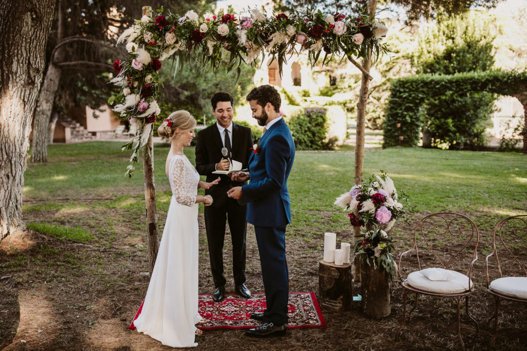bride and groom exchange rings in front of outdoor altar