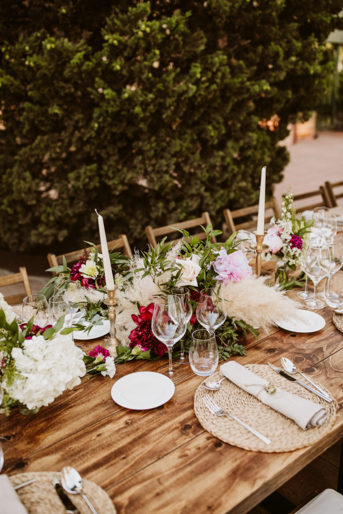 table setting with brass candlesticks, white candles, pink and red flowers, and pampas grass