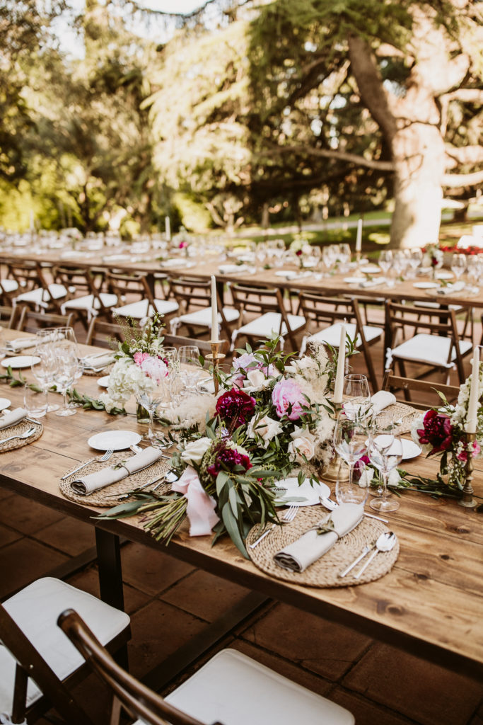 table setting with pink and red flowers, white candles in brass candlesticks, jute mats, and pampas grass