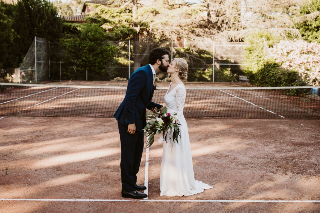 bride and groom kiss on tennis court