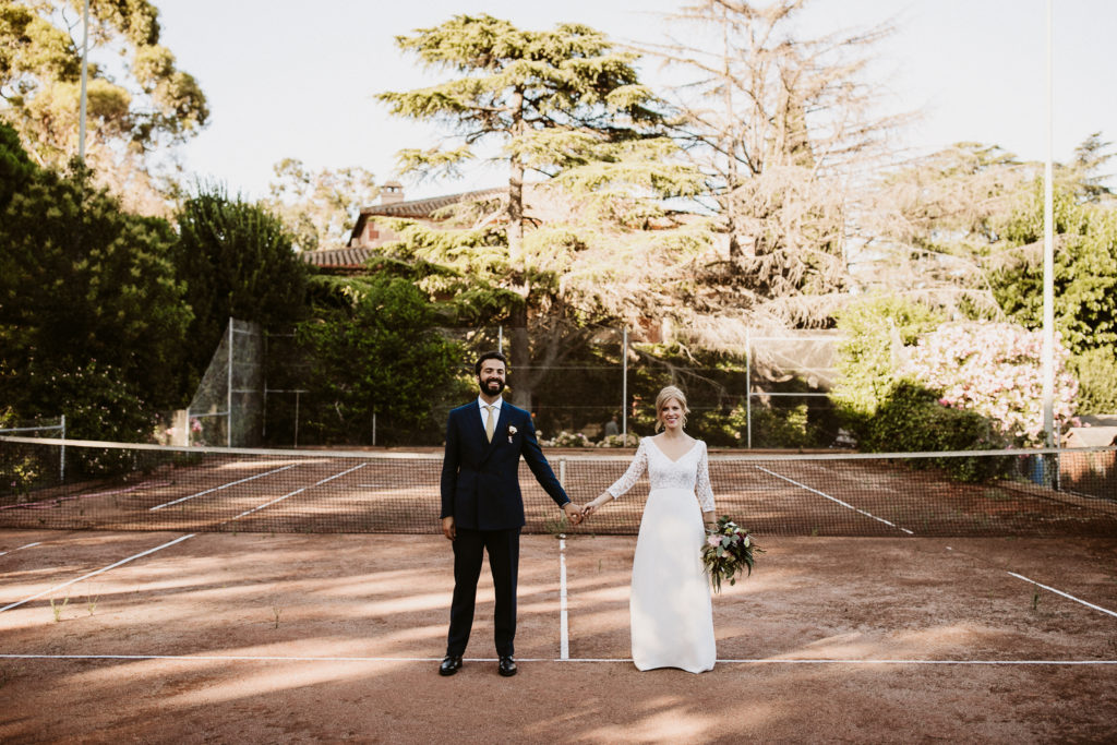bride and groom hold hands on tennis court