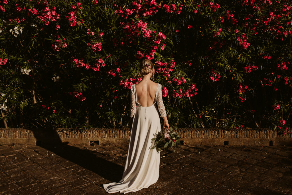 bride facing red flowering trees
