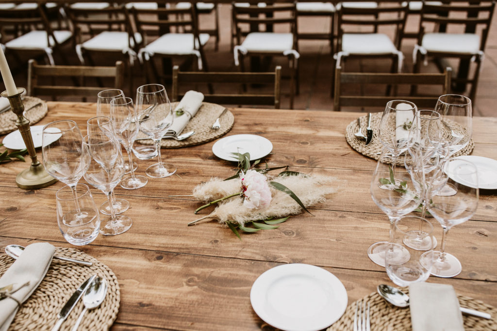 wooden table covered in glassware, jute mats, wild grass, and a pink flower