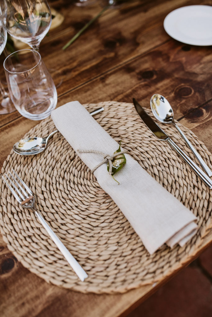place setting with jute mat, silverware, linen napkin ties with natural string and name tag written on leaf
