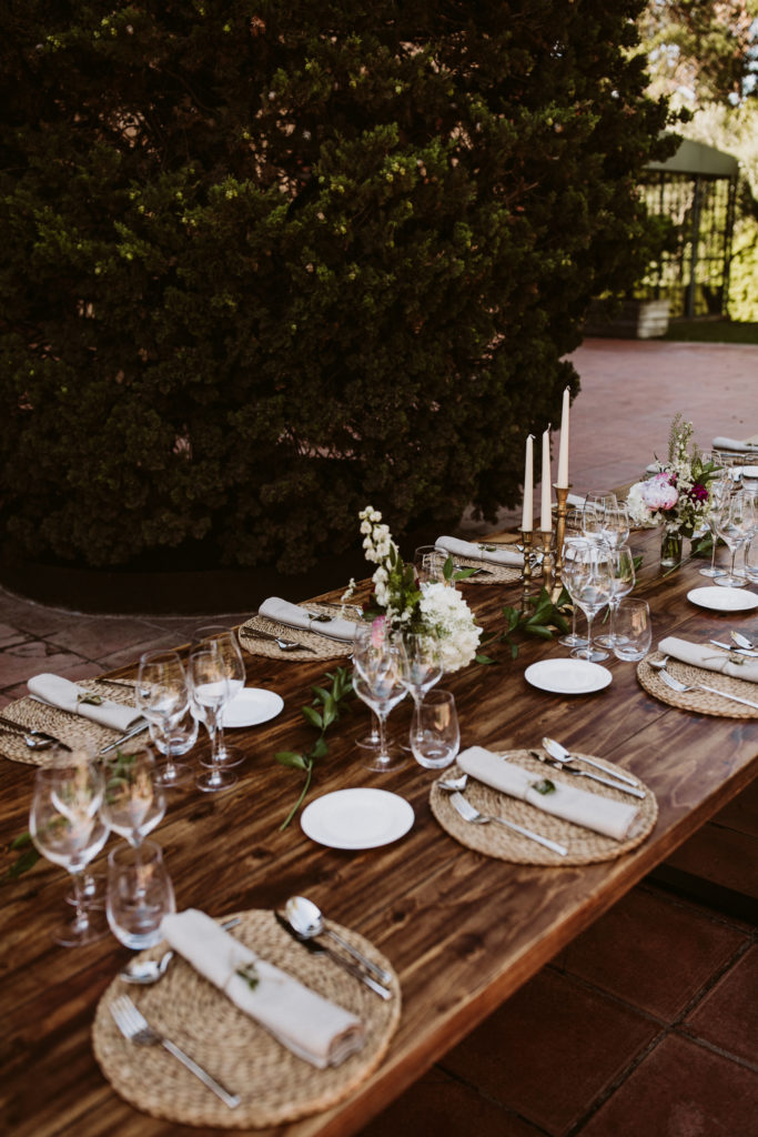 wooden table covered in place settings made of jute mats, linen napkins, silverware, and simple flowers