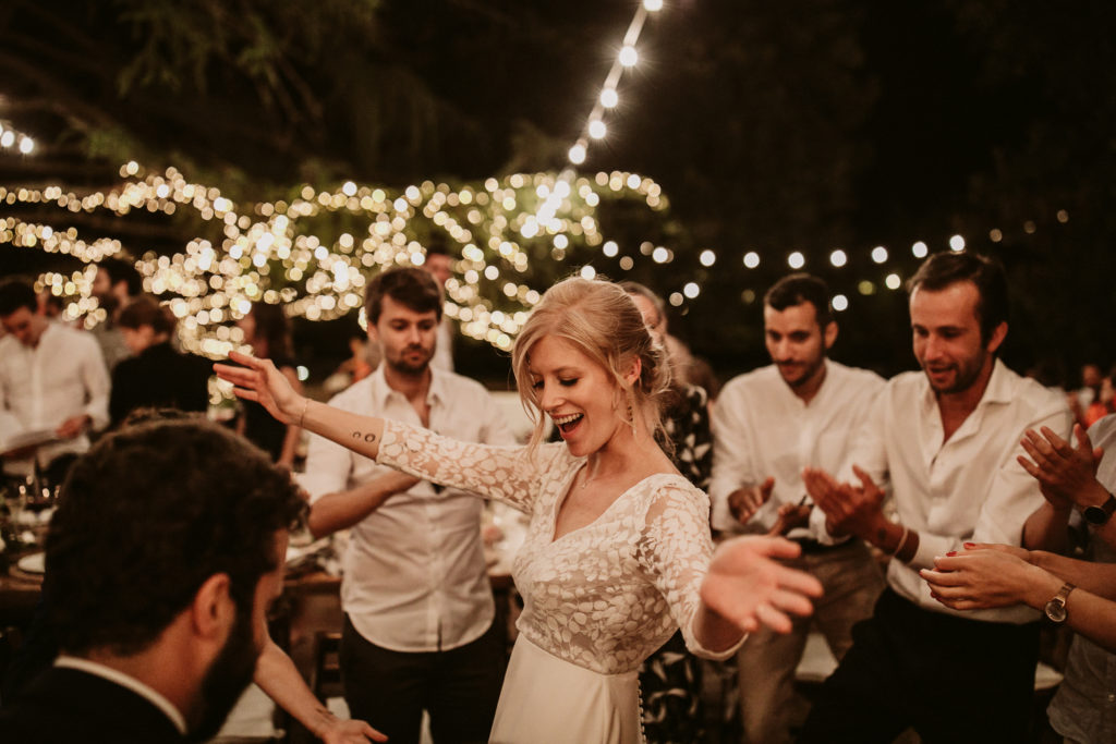 bride and groom dance while surrounded by guests
