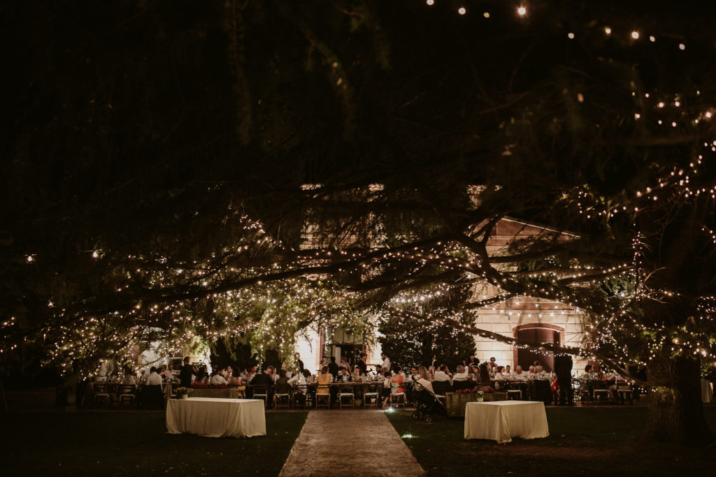 wedding guests dine outside underneath twinkly lights