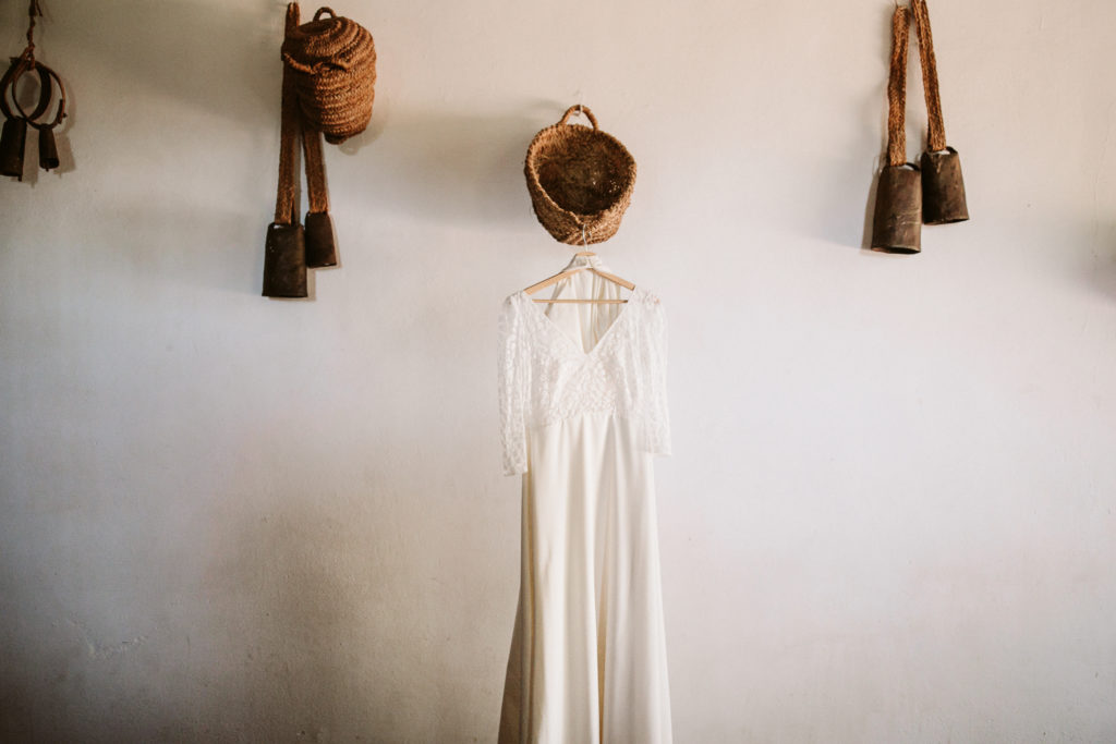 wedding dress hanging from basket on the wall