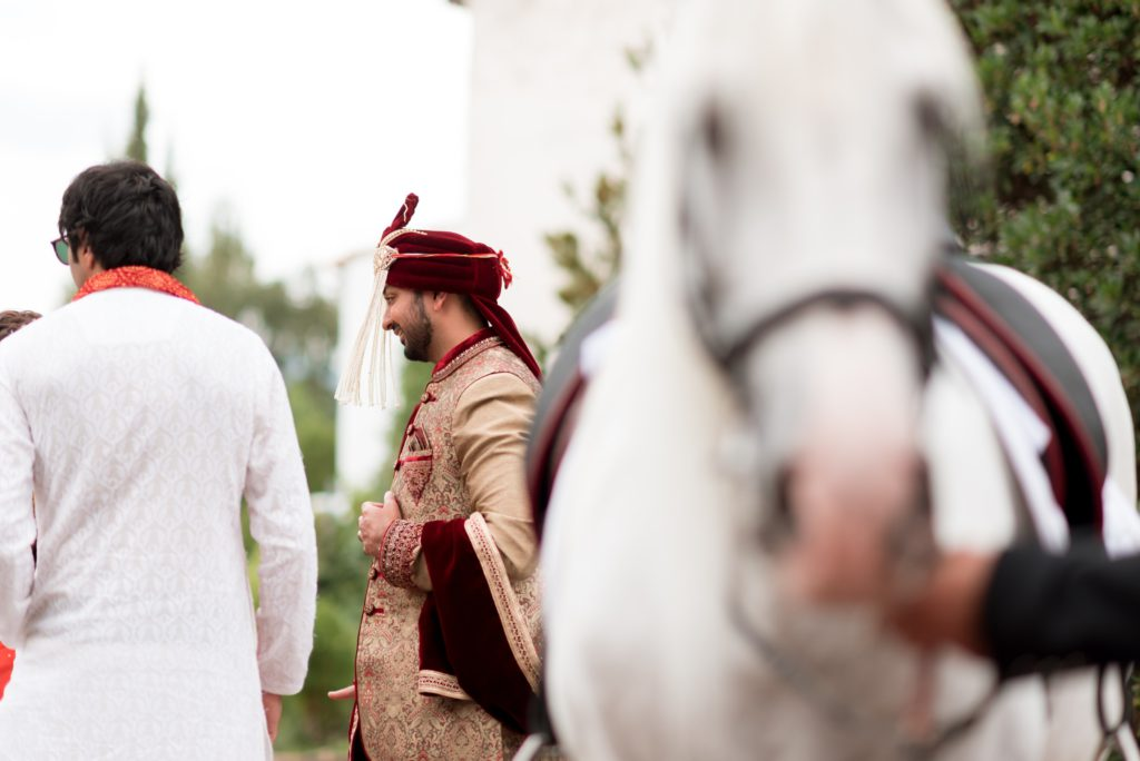 Groom in traditional Hindu clothing with white horse