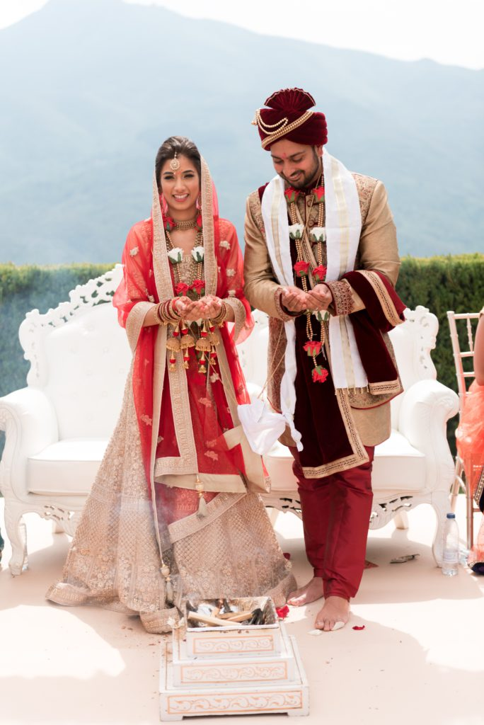 Hindi bride and groom stand behind incense in traditional clothing and palms extended