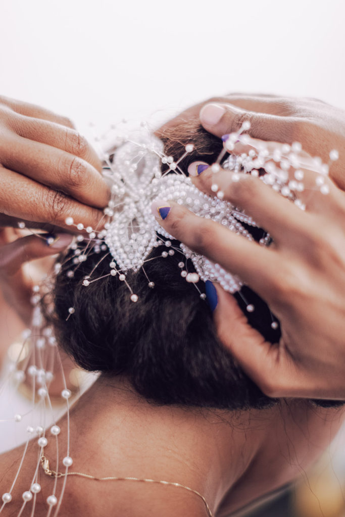 bride pins pearl headpiece into place while getting ready for her wedding