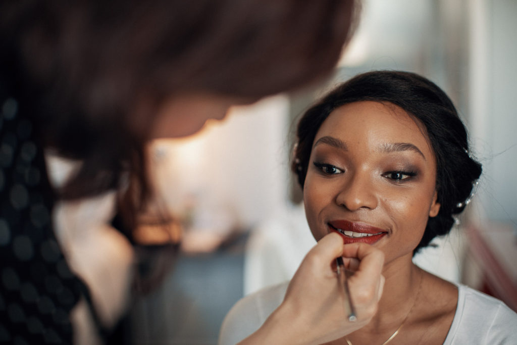 bridal beauty with bride having her makeup done by makeup artist