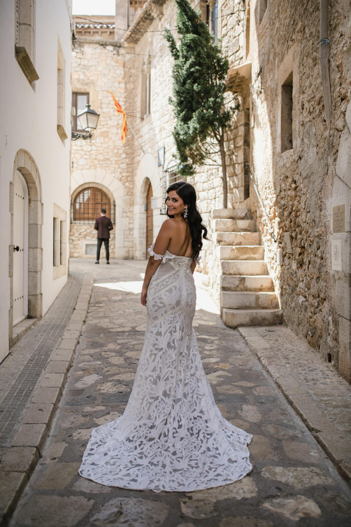bride showing off her beautiful lace dress in the streets of Sitges, Spain